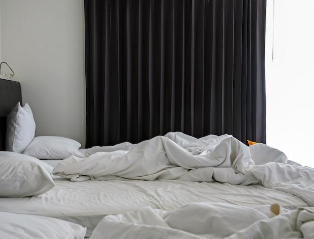 Cama desarrumada amarrotada do interior branco do quarto