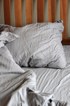 Cama desarrumada vazia de manhã com roupa de cama de cor cinza escuro, roupas de cama. lençol, cobertor, travesseiros e cabeceira de madeira. foco seletivo suave. espaço da cópia do texto.