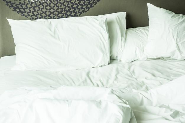Cama desarrumado com lençóis brancos