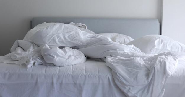 Cama desfeita branca com cobertor desarrumado amassado e travesseiro na luz da manhã