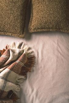 Cama desfeita com travesseiro e manta.
