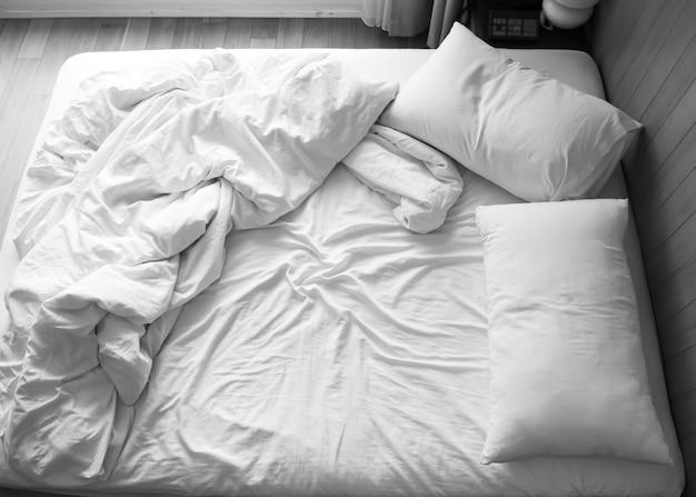 Cama desfeita no quarto. tom de cor preto e branco