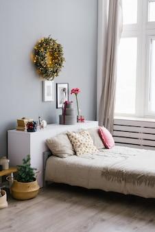 Cama grande com almofadas no quarto, decorada para o natal e ano novo