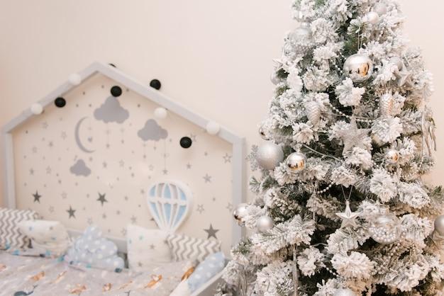 Cama infantil cinza branco de madeira em forma de uma casa com estrelas e lua, um balão na parede ao lado de uma árvore de natal, foco seletivo