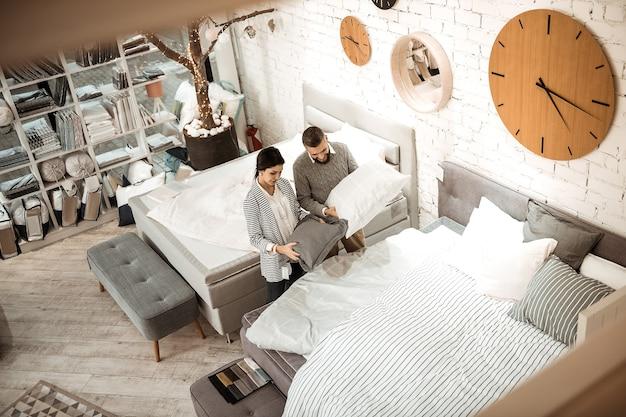 Cama king-size. casal bonito e atencioso observando a qualidade dos travesseiros apresentados enquanto fica em um showroom bem equipado