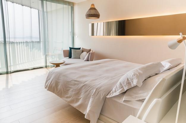 Cama king size com lençóis brancos e travesseiro na cama em quarto de hotel.