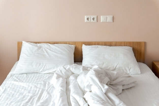 Cama macia desfeita com um cobertor branco e travesseiros. limpeza da cama, conceito de cama limpa