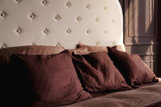 Cama marrom do quarto de hotel com muitos travesseiros.