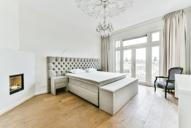 Cama moderna com colchão confortável e travesseiros macios localizados perto da mesa de cabeceira e lareira elétrica em quarto espaçoso