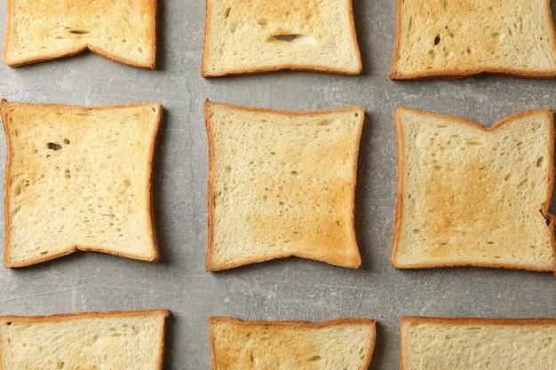 Cama plana com torradas de pão em fundo cinza