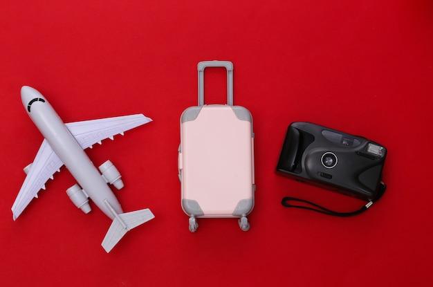 Cama plana de viagem. mini mala de viagem de plástico, câmera, avião de ar sobre fundo vermelho. estilo mínimo. vista do topo