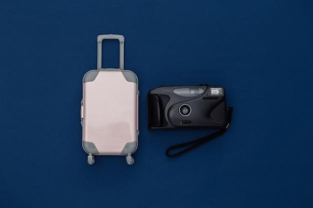 Cama plana de viagem. mini mala de viagem de plástico, câmera no fundo azul clássico. estilo mínimo. vista do topo