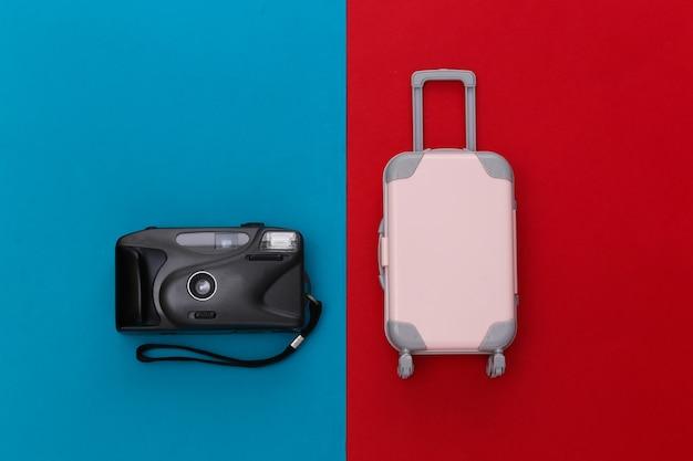 Cama plana de viagem. mini mala de viagem de plástico, câmera sobre fundo azul vermelho. estilo mínimo. vista do topo