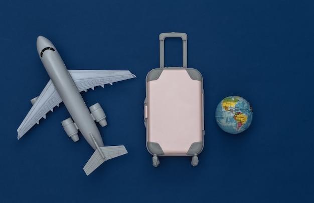 Cama plana de viagem. mini mala de viagem de plástico, globo, avião de ar no fundo azul clássico. estilo mínimo. vista do topo