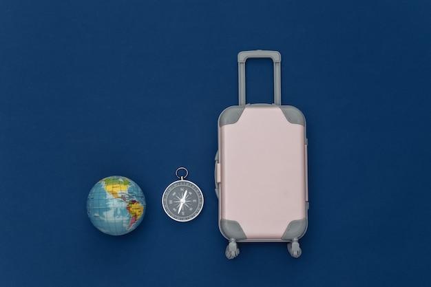 Cama plana de viagem. mini mala de viagem de plástico, globo, bússola no fundo azul clássico. estilo mínimo. vista do topo