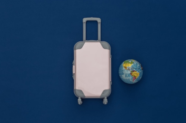 Cama plana de viagem. mini mala de viagem de plástico, globo no fundo azul clássico. estilo mínimo. vista do topo
