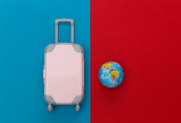 Cama plana de viagem. mini mala de viagem de plástico, globo sobre fundo azul vermelho. estilo mínimo. vista do topo