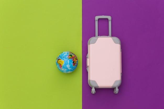 Cama plana de viagem. mini mala de viagem de plástico, globo sobre fundo roxo verde. estilo mínimo. vista do topo