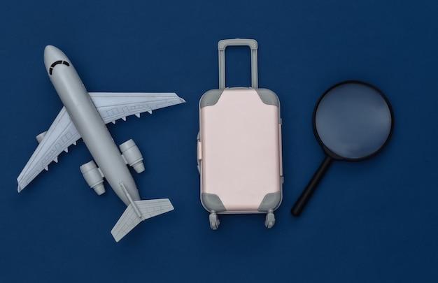 Cama plana de viagem. mini mala de viagem de plástico, lupa, avião de ar no fundo azul clássico. estilo mínimo. vista do topo