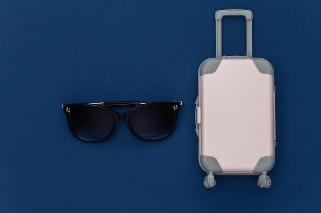 Cama plana de viagem. mini mala de viagem de plástico, óculos de sol sobre fundo azul clássico. estilo mínimo. vista do topo