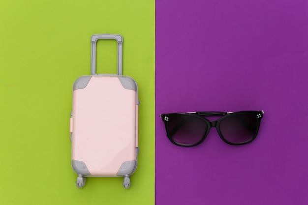 Cama plana de viagem. mini mala de viagem de plástico, óculos de sol sobre fundo verde roxo. estilo mínimo. vista do topo