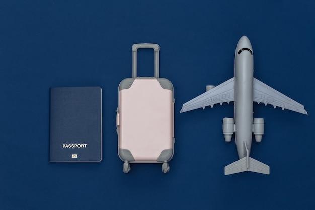 Cama plana de viagem. mini mala de viagem de plástico, passaporte, avião no fundo azul clássico. estilo mínimo. vista do topo