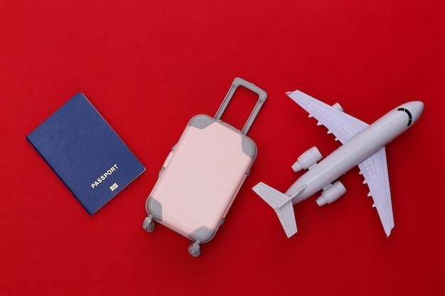 Cama plana de viagem. mini mala de viagem de plástico, passaporte, avião sobre fundo vermelho. estilo mínimo. vista do topo