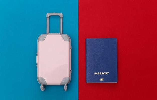 Cama plana de viagem. mini mala de viagem de plástico, passaporte com fundo azul vermelho. estilo mínimo. vista do topo