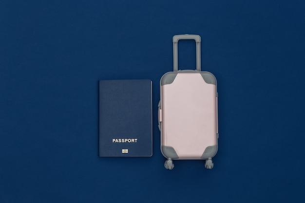 Cama plana de viagem. mini mala de viagem de plástico, passaporte em fundo azul clássico. estilo mínimo. vista do topo