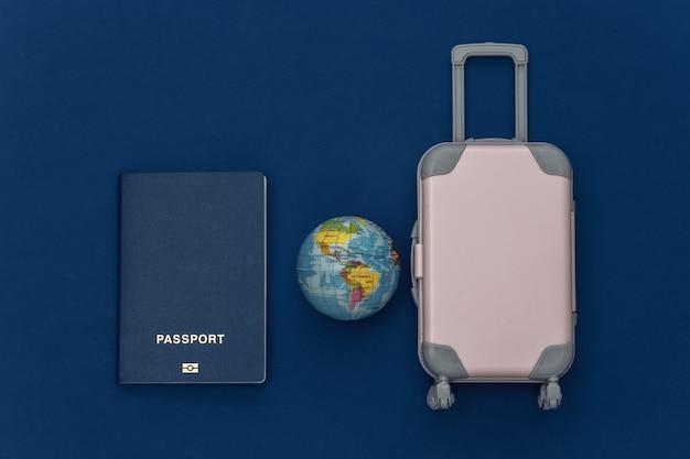 Cama plana de viagem. mini mala de viagem de plástico, passaporte, globo no fundo azul clássico. estilo mínimo. vista do topo