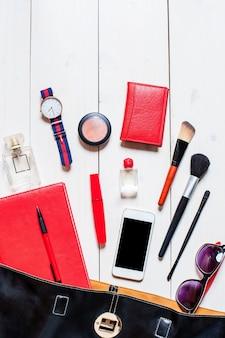 Cama plana, vista superior, simulação de cosméticos e acessórios femininos caíram da bolsa preta sobre fundo branco. telefone, óculos, relógio, caderno, caneta