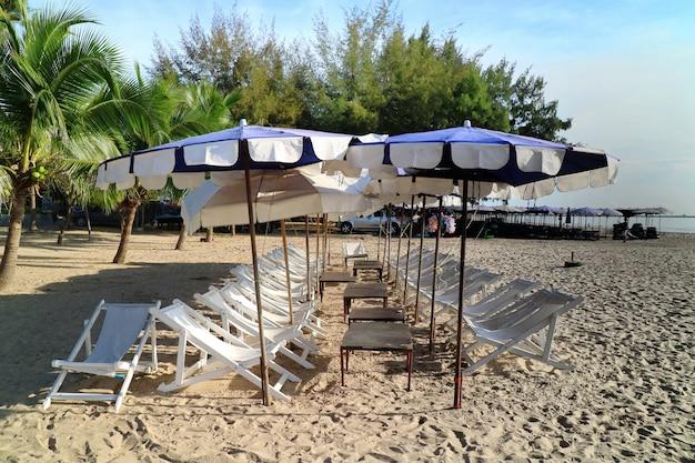 Cama praia, guarda-chuva e algum lixo de plástico na praia tropical com pinheiro no verão.