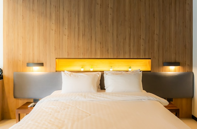 Cama queen size coberta com um edredom branco e quatro travesseiros colocados na cama.