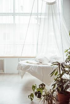 Cama redonda branca com almofadas suspensas na casa