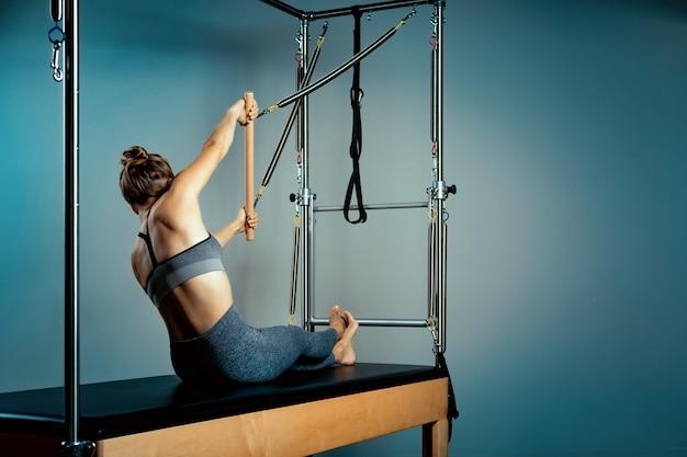 Cama reformador pilates, close-up, mulher e instrutor fazendo exercício no simulador reformador para tratamento do sistema musculoesquelético.