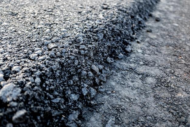 Camada de asfalto acabou de se espalhar em uma nova estrada, detalhe