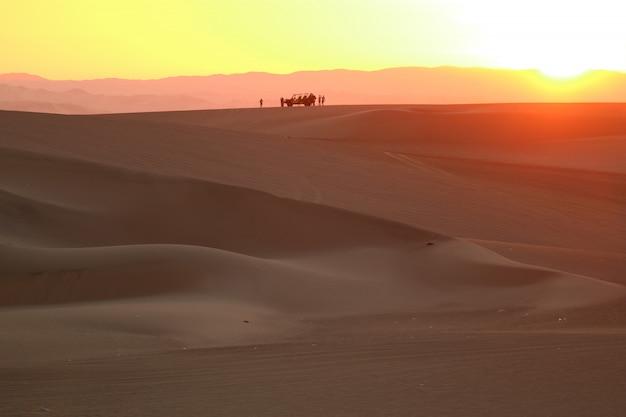 Camada de cor lindo pôr do sol sobre a duna de areia do deserto de huacachina com a silhueta da duna baggy e as pessoas