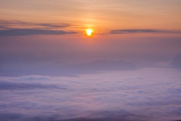 Camada de montanhas na neblina na hora do nascer do sol