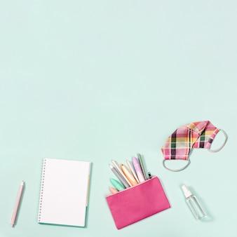Camada plana com caderno e papelaria para máscara de tecido rosa feminino para proteção contra infecções e desinfetante para as mãos