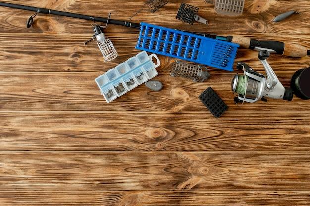 Camada plana com equipamento de pesca, vara de pesca e caixa de plástico com equipamento de pesca e ganchos