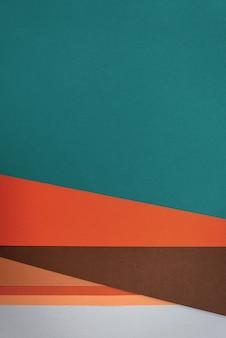 Camada plana com papéis texturizados em tons vintage, como azul-esverdeado, laranja e ocre