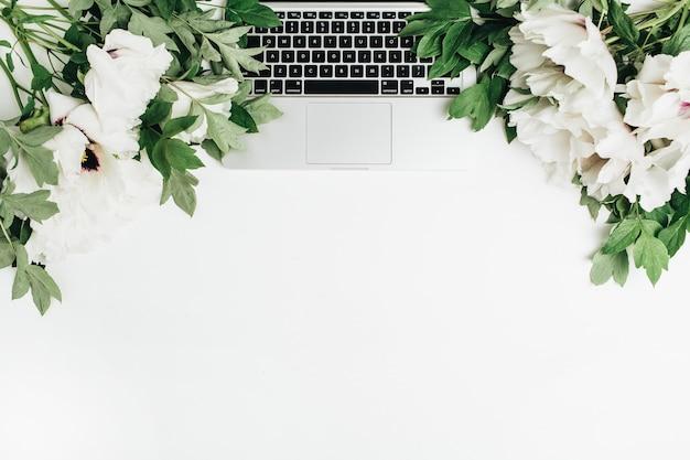 Camada plana, composição de vista superior com laptop e flores de peônias brancas na superfície branca