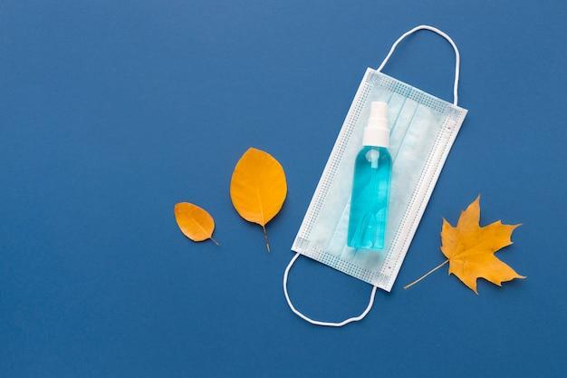 Camada plana da máscara médica com desinfetante para as mãos e folhas de outono