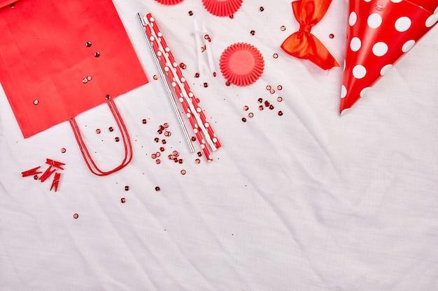 Camada plana de aniversário, vista superior e espaço de cópia para texto, quadro ou plano de fundo com itens vermelhos do festival, chapéus de festa e fitas, cartão de aniversário ou festa