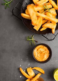 Camada plana de batatas fritas na grelha de resfriamento com mostarda