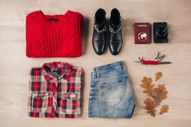 Camada plana de estilo feminino e acessórios, suéter de malha vermelha, camisa xadrez, jeans, botas de couro preto, tendência da moda outono, câmera fotográfica vintage, faca suíça, passaporte, roupa de viajante