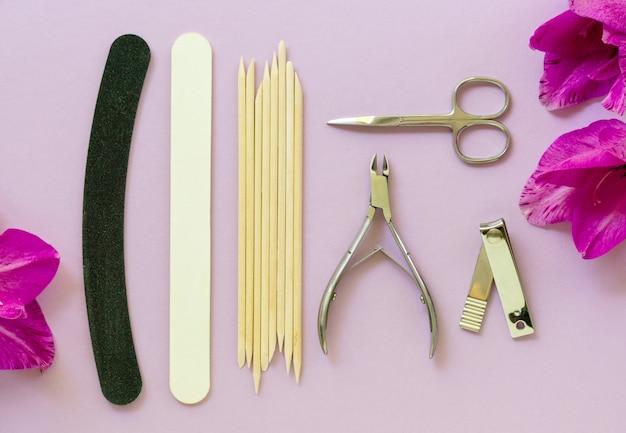 Camada plana de ferramentas para manicure e pedicure em uma mesa lilás