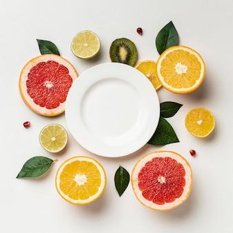 Camada plana de frutas cítricas com prato