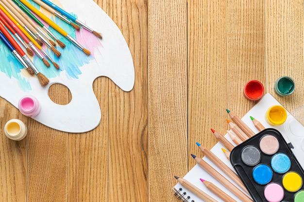 Camada plana de fundamentos de pintura com pincéis e paleta de tinta