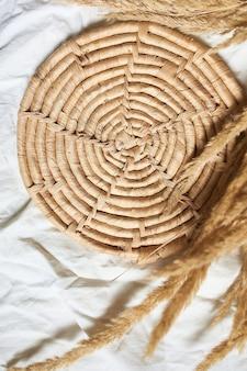 Camada plana de grama bege de pampa no fundo da toalha de mesa de linho têxtil branco, belo padrão com cores neutras, mínimo, elegante, conceito de tendência, vista superior